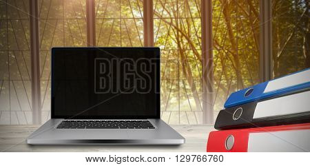 Desk with laptop against view of a tree