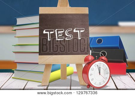Test word against red apple on pile of books in classroom