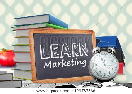 Learn Marketing word against red apple on pile of books
