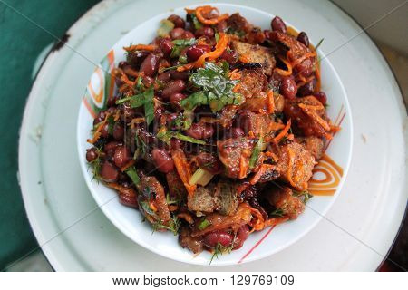 light vegetarian salad from red beans and dry rye bread with green under tomato souce