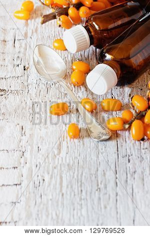 Sea buckthorn oil in a bottle and fresh sea buckthorn on a white wooden background. Alternative medicine. Copy space background. Selective focus