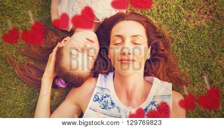 Composite image of mother and daughter lying on a park behind heart tinsel