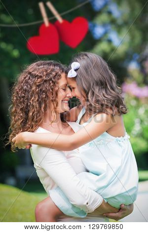 Composite image of mother and daughter holding each other behind heart tinsel