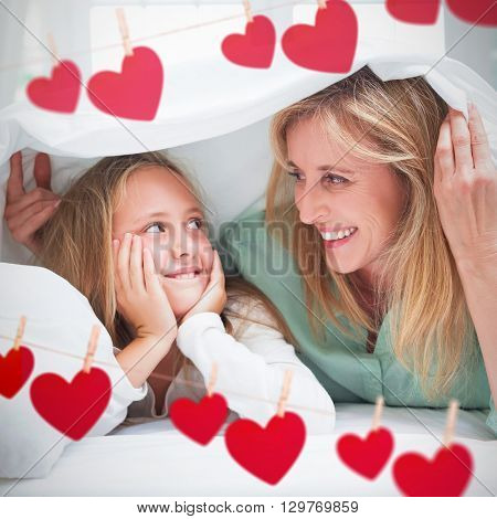 Hearts hanging on a line against mother and daughter looking at each other under the duvet