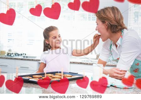 Hearts hanging on a line against mother and daughter with hot fresh cookies