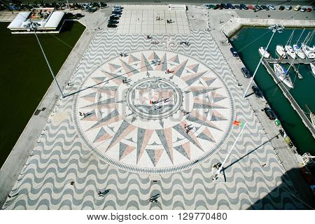 aerial view of big compass rose and mappa mundi or world map in floor next to Monument to Discoveries or Padrao dos Descobrimentos public landmark in street of Belem Lisbon Portugal