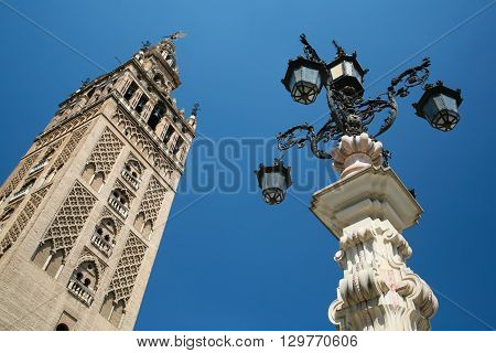 famous belfry named Giralda in landmark catholic cathedral Saint Mary of the See public gothic monument year 1507 World Heritage UNESCO and old vintage streetlight in Seville Andalusia Spain