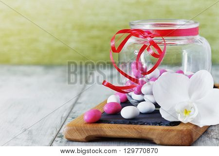 Candy with colored glaze in a glass jar. Delicious sweet buffet. Holidays and events. Selective focus. Toned image