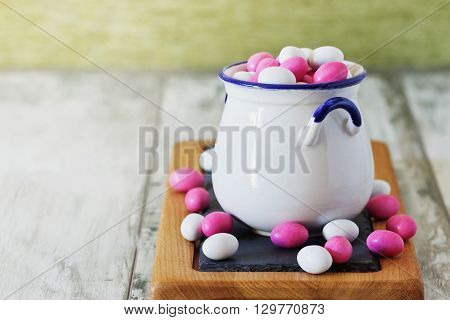 Candy with colored glaze in ceramic pot. Children's joy. Selective focus