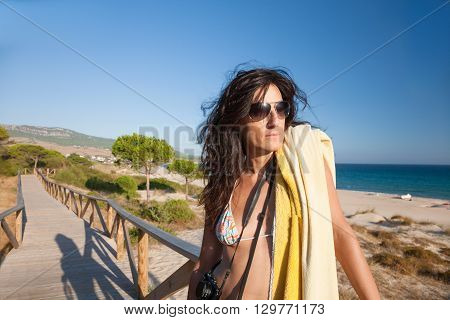 portrait of brunette summer vacation woman with sunglasses bikini and yellow towel posing in wooden walkway with blue sky in Bolonia sand beach in Tarifa Cadiz Andalusia Spain Europe