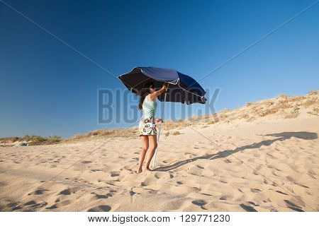 mini skirt and shirt brunette summer vacation woman opening blue parasol in sand dune with blue sky in Palmar beach in Vejer Cadiz Andalusia Spain Europe