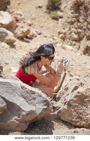 brunette woman with green and red shirt crouching looking to camera as photographer taking photo picture in Teide mountain Tenerife Canary Islands Spain Europe