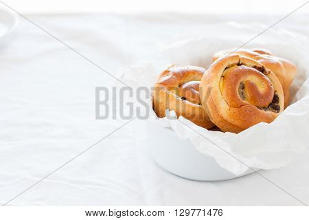 Fresh baked vanilla sweet sugar buns with chocolate drops in a bowl on a wooden background with place for text, horizontal
