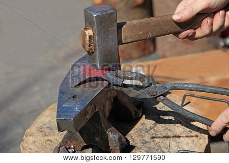 Forging steel billet on the anvil with a hammer