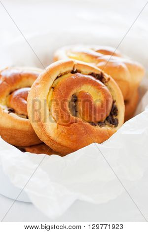 Fresh baked vanilla sweet sugar buns with chocolate drops in a crate on a wooden background, closeup