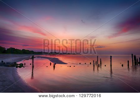 Old broken pier at sunset on the coast of the Baltic sea, Latvia