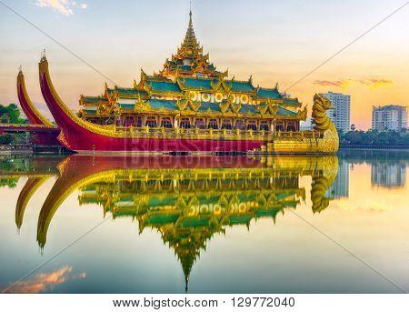 Golden Karaweik palace reflecting on Kandawgyi lake looks like an ancient royal barge. Sunset time. Yangon, Myanmar