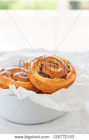 Fresh baked vanilla sweet sugar buns with chocolate drops in a bowl on a wooden background closeup