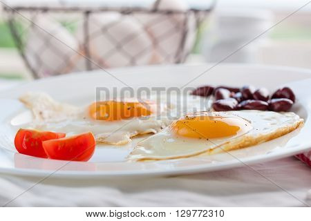 Homemade fried eggs with tomatoes and red kidney beans on a plate on a table with kitchen background, closeup