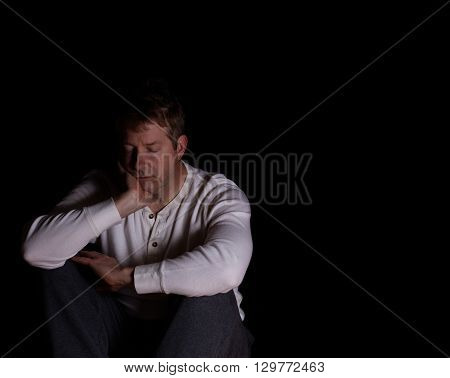 Depressed mature man eyes closed and resting head in right hand. Dark background with copy space available.