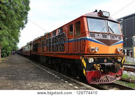 orange train on railway station wait to travel
