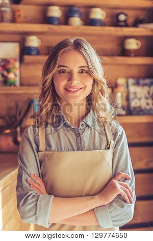 Beautiful young waitress in apron is looking at camera and smiling while standing with crossed arms in the cafe