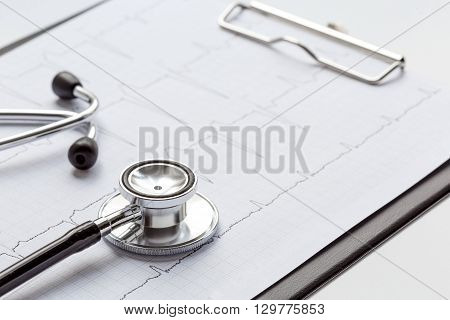 new stethoscope on a white background with cardiogram close up