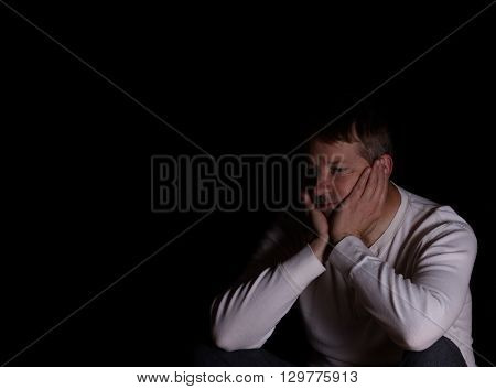 Depressed mature man looking away from camera holding his head in both hands. Dark background with copy space available.