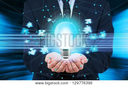 Idea concept with businessman holding lightbulb with puzzle pieces around on abstract blue background