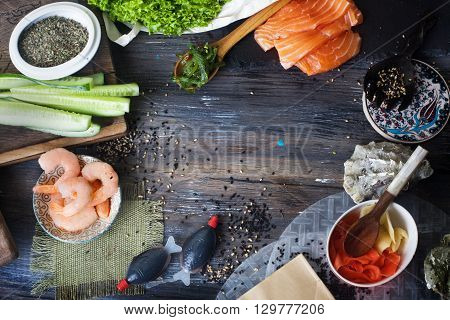 Food background, a wooden table top, sushi rolls cucumbers Chuka ginger, shrimp salmon seaweed