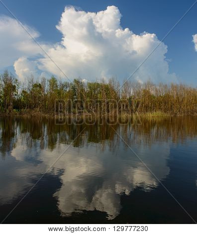 clouds reflected in the water of the river spring landscape