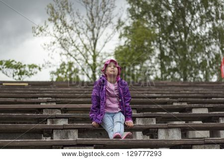 Sad little girl is sitting on the bench.