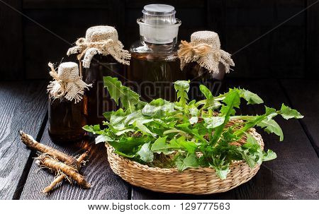 Medicinal plant - dandelion. Dandelion leaves in a basket tincture and syrup in pharmaceutical bottles roots on wooden background. It is used for herbal medicine and healthy food