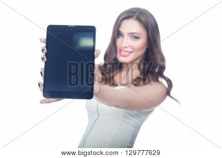 Girl blurred holding tablet computer and shows it.