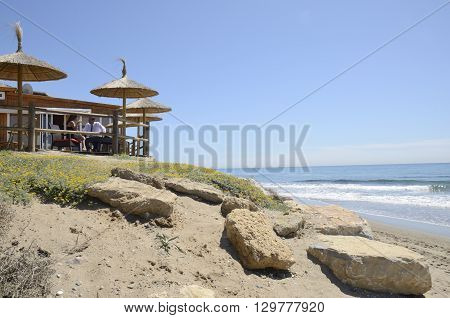 MARBELLA, SPAIN -APRIL 9, 2016: Couple having lunch at sun in the terrace of a beach bar in Marbella a city in southern Spain belonging to the province of Malaga Andalusia Spain