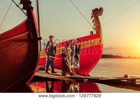 North Princess And Two Warriors With Swords On The Sailing Ships Background.