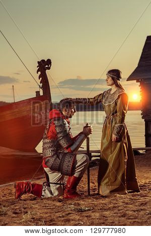 North princess is blessing the warrior. Warships on the background.