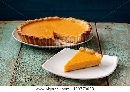 Homemade oldfashioned round pumpkin pie on old table painted blue horizontal
