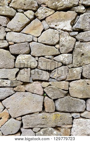Ancient wall of stones built with blocks of Trachyte and Tuff.Texture.