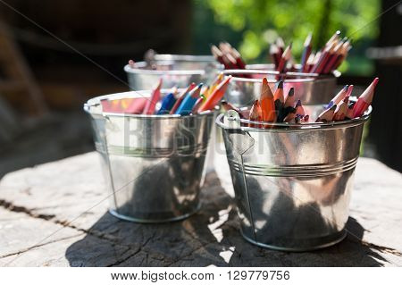 Colorful pencils in metal buckets on wooden stump