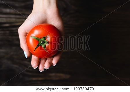 tomato in hand on a wooden background