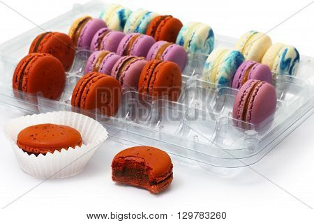 A few varicolored macaroon biscuit are in plastic box over white background.