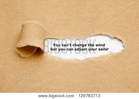 Motivational quote You can not change the wind but you can adjust your sails appearing behind torn paper.
