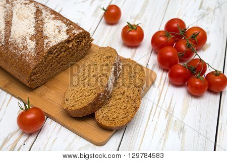 Pieces of homemade bread and tomatoes on table