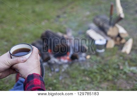 Man Prepares Coffee On A Fire In A Tent Camp.