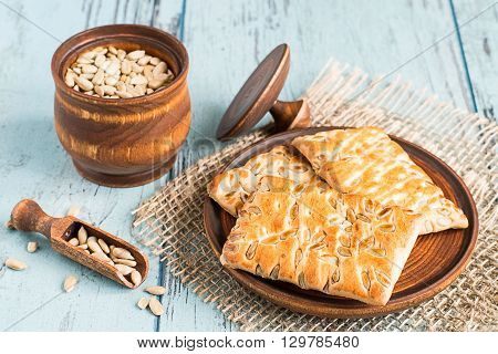 Peeled sunflower seeds in a wooden pot and cookies with sunflower seeds on a wooden plate on a blue background.