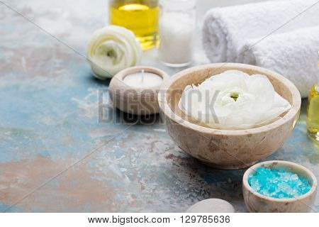 Spa and wellness massage setting, white floating ranunculus flowers Still life with essential oil, salt and stones