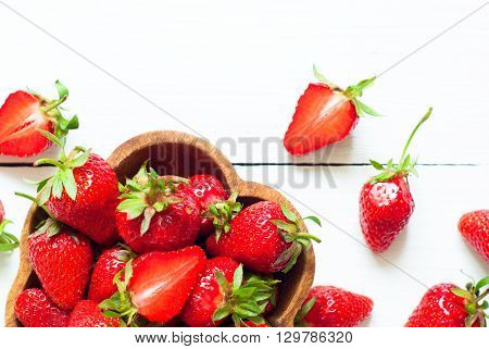 Fresh strawberries in woden bowl at white wooden table. View from above with copy space.