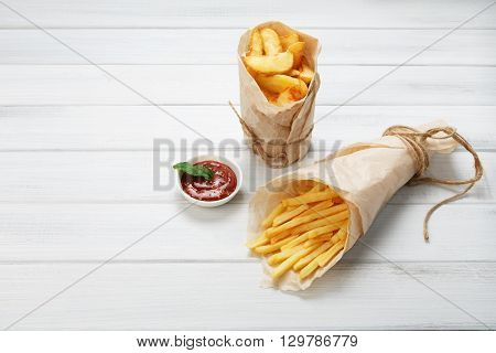 Potato wedges and french fries wrapped in brown wrapping paper. Fast food take away at white shabby chic wood. Fried potatoes with tomato sauce. Chips, potato slices. Top view with copyspace