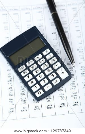 Calculator with pen, on sheet of paper